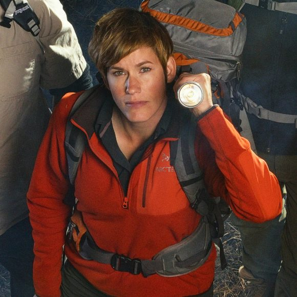 Research biologist Ranae Holland holding a flashlight and dressed in hiking gear