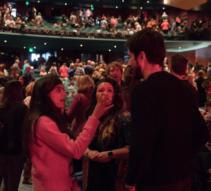 Audience inside the McCaw Hall auditorium talking to one another