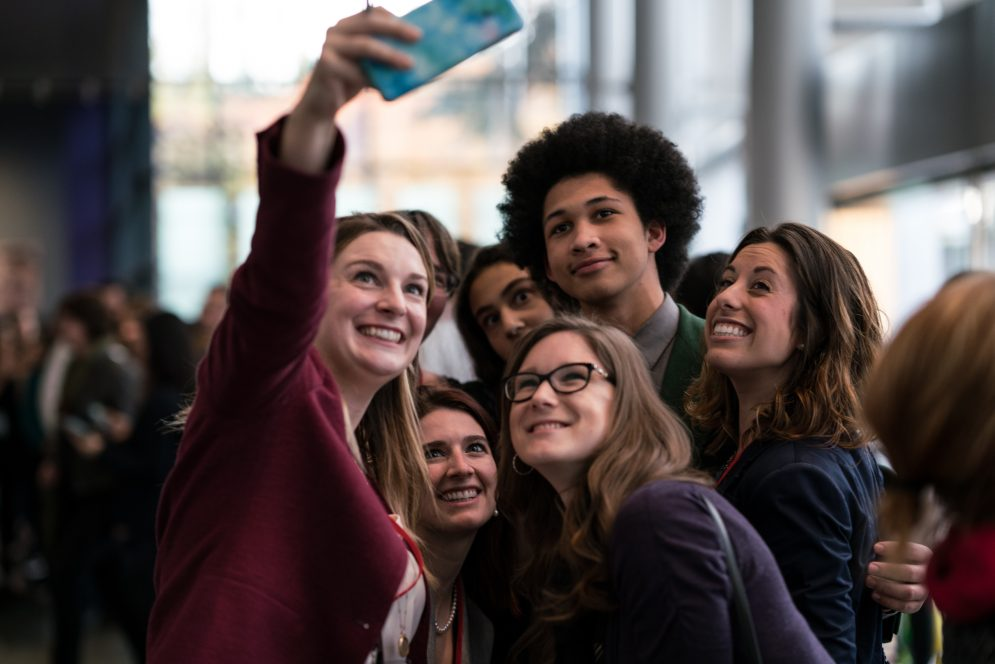 Group of people taking a selfie in the audience lobby