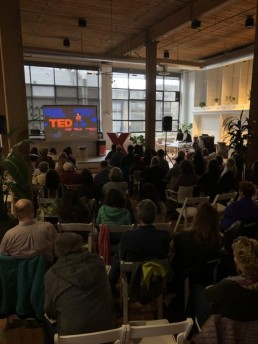 Back of the room at The Riveter as the audience watches TEDxSeattleLive on the large screen