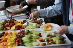 A man is selecting fresh fruit from a table of food