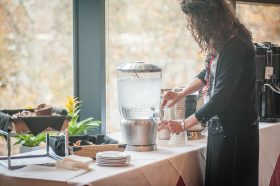 Woman pours ice water from a pitcher at a table with coffee, tea, and muffins.