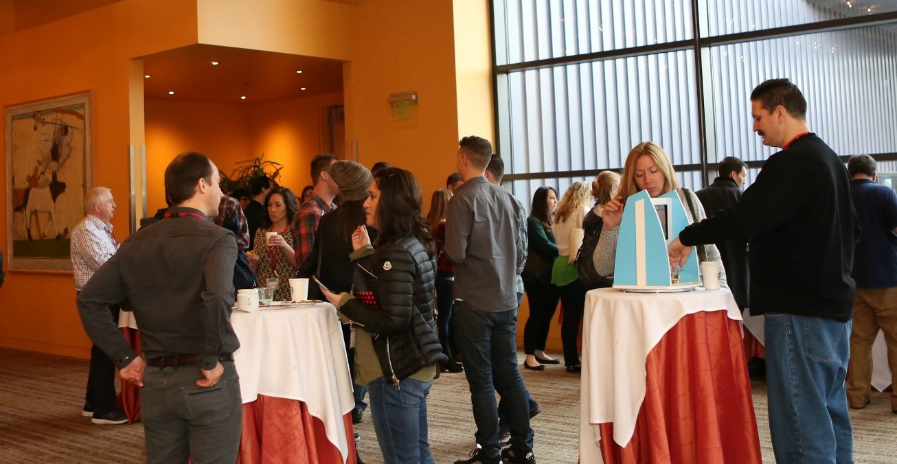 Wide shot of people in the Patron Lounge standing at cocktail tables during a session break at TEDxSeattle